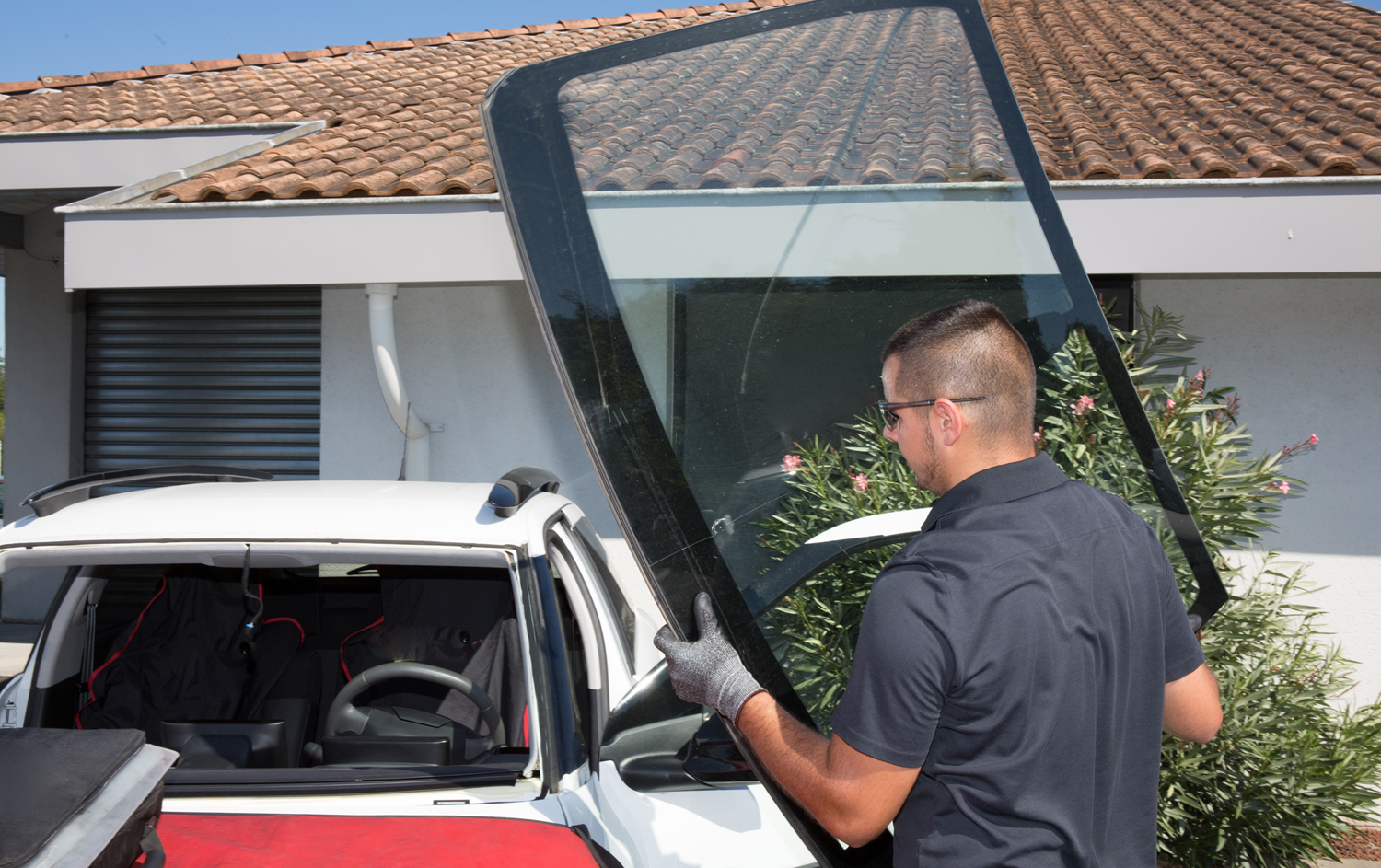 Technician Holding Windshield for Replacement on Car in Mesa AZ